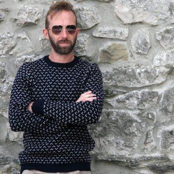 model wearing Glencroft navy Saxon british wool jumper against wall