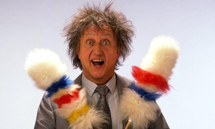 Ken Dodd holding two sheepskin lambswool tickling stick dusters